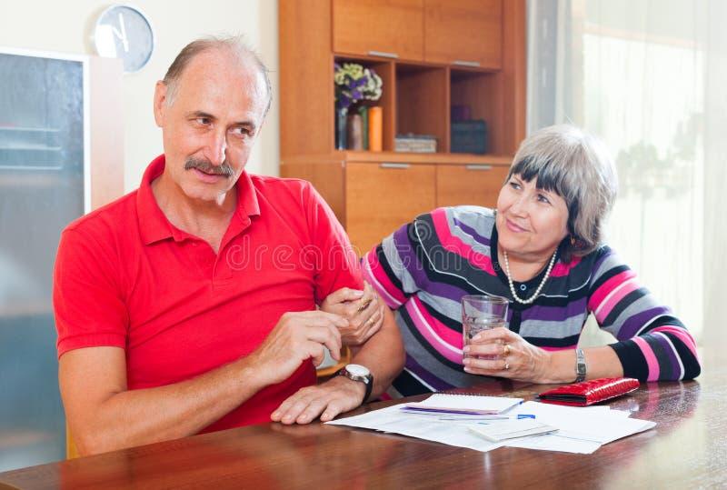 有成熟的夫妇在财政文件的争吵 免版税库存照片