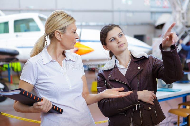 有成熟辅导员的确信的年轻女性飞行员 免版税库存照片