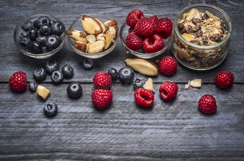 有成份的玻璃碗健康早餐- muesli、莓果和坚果在蓝色土气木背景 免版税库存照片