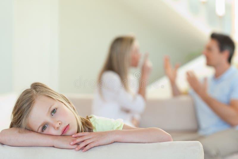 有战斗的哀伤的女孩在背景中做父母 免版税库存图片