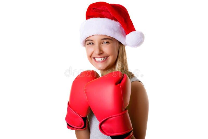 有战斗的手套的运动的愉快的女孩佩带的圣诞节圣诞老人帽子,被隔绝 库存照片
