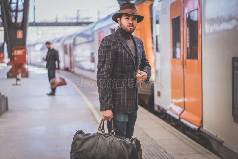 有戴便衣和帽子的旅行袋子的可爱的确信的西班牙商人等待在的火车 免版税库存照片