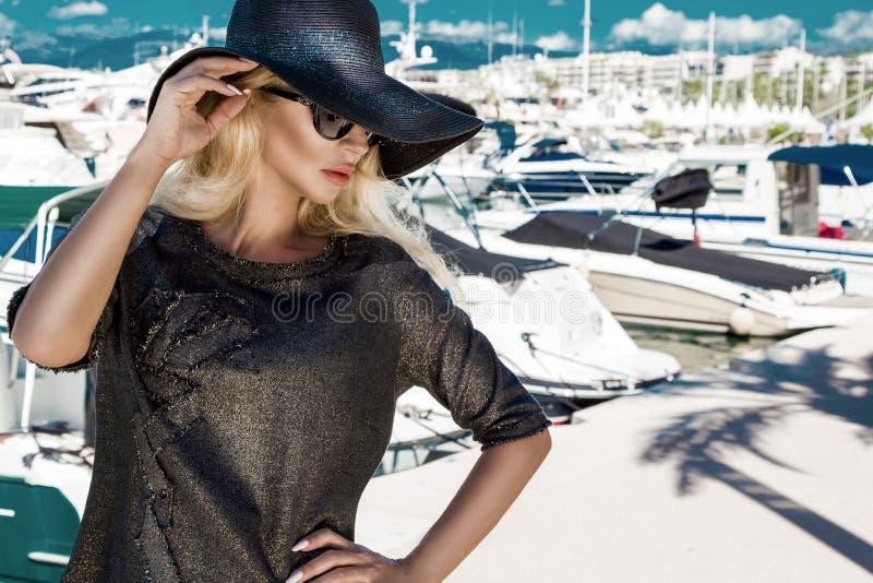 有戴眼镜的完善的面孔的画象美丽的现象惊人的典雅的性感的白肤金发的式样妇女站立与典雅的隋 库存图片