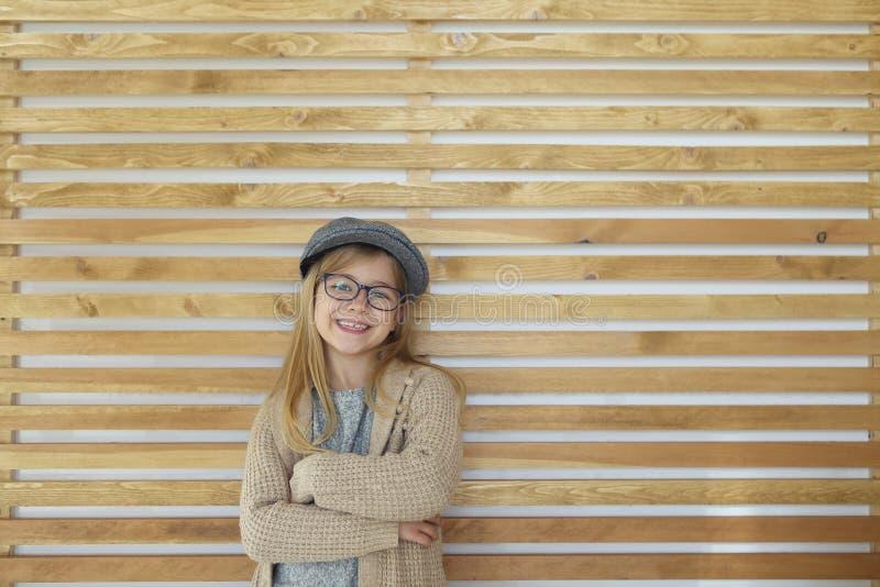 有戴着在木背景的黑镜片的微笑的逗人喜爱的女孩帽子 库存图片