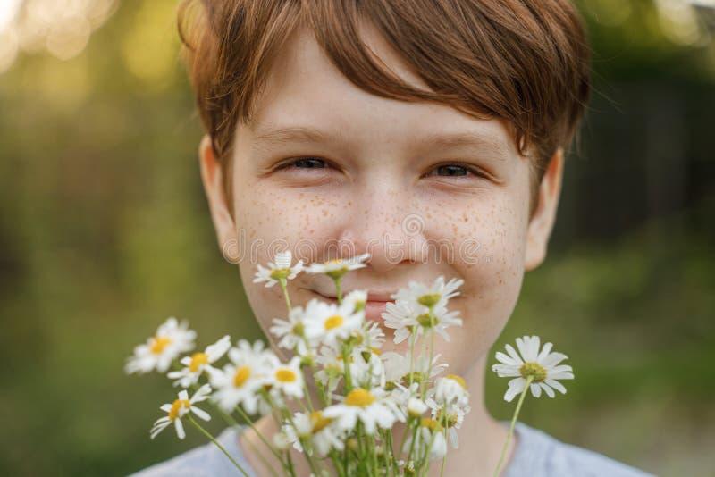 有戴西花束的微笑的孩子  库存图片