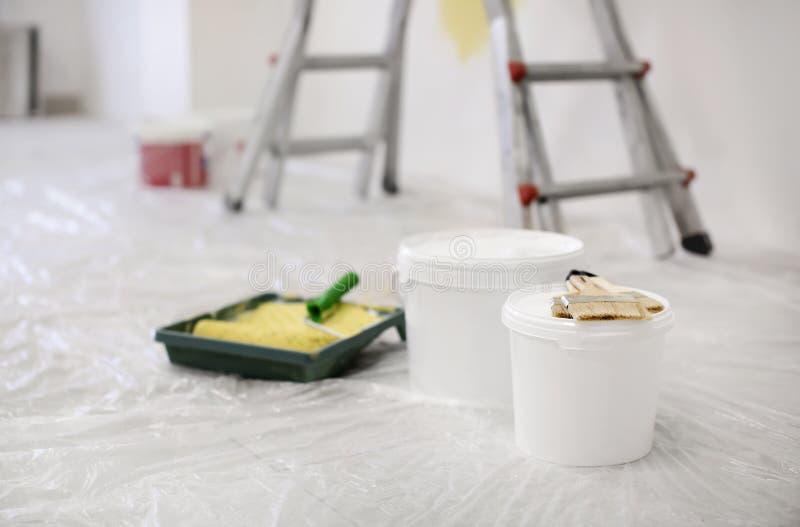 有户内户内油漆和刷子的桶 图库摄影
