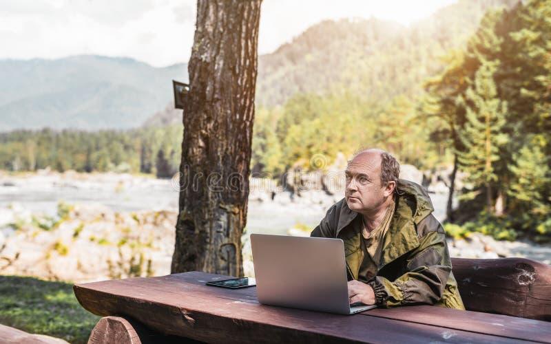 有户外他的膝上型计算机的男性林务员 免版税库存图片