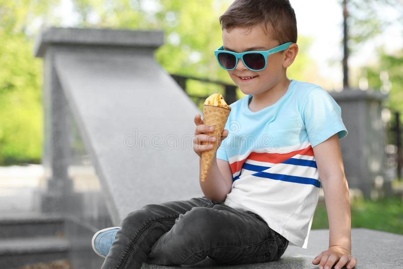 有户外可口冰淇淋的逗人喜爱的小男孩 图库摄影
