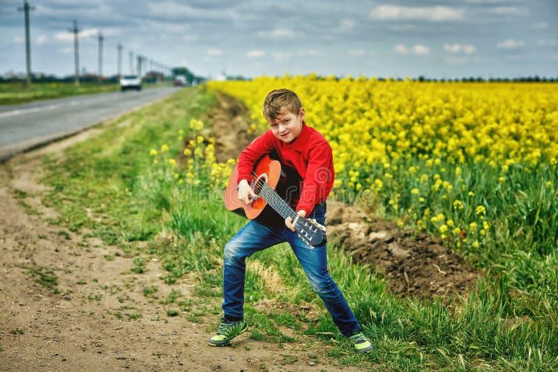 有户外声学吉他的男孩 图库摄影