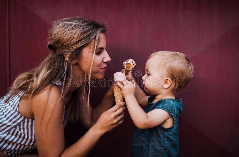 有户外小小孩女孩的年轻母亲在夏天,吃冰淇淋 免版税库存照片