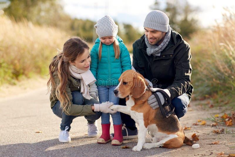有户外小猎犬狗的幸福家庭在秋天 免版税图库摄影