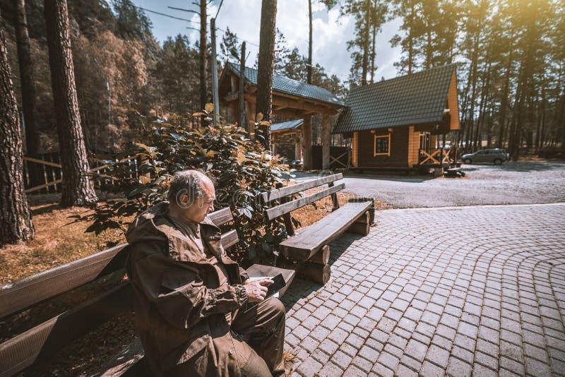 有户外数字式片剂的老人在木头 库存照片
