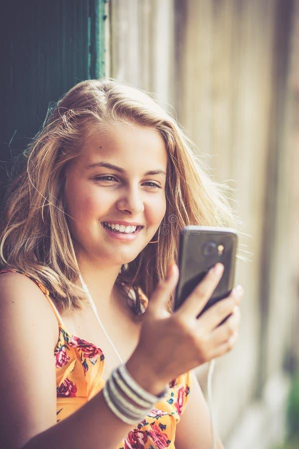 有户外智能手机的女孩 免版税库存照片