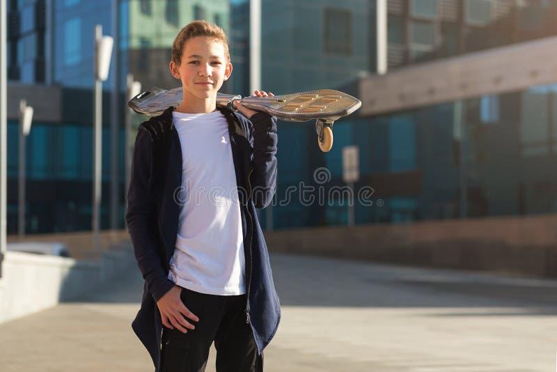 有户外滑板的逗人喜爱的青少年的男孩,站立在街道上 免版税库存照片