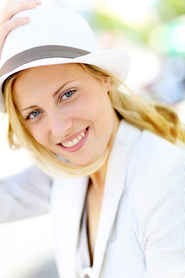 有户外白色帽子的美丽的少妇 免版税库存图片