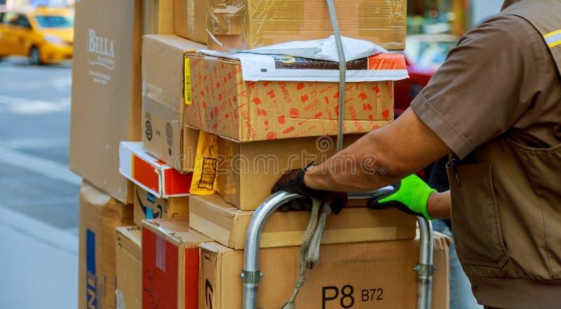 有户外箱子的年轻男性送货员 库存照片