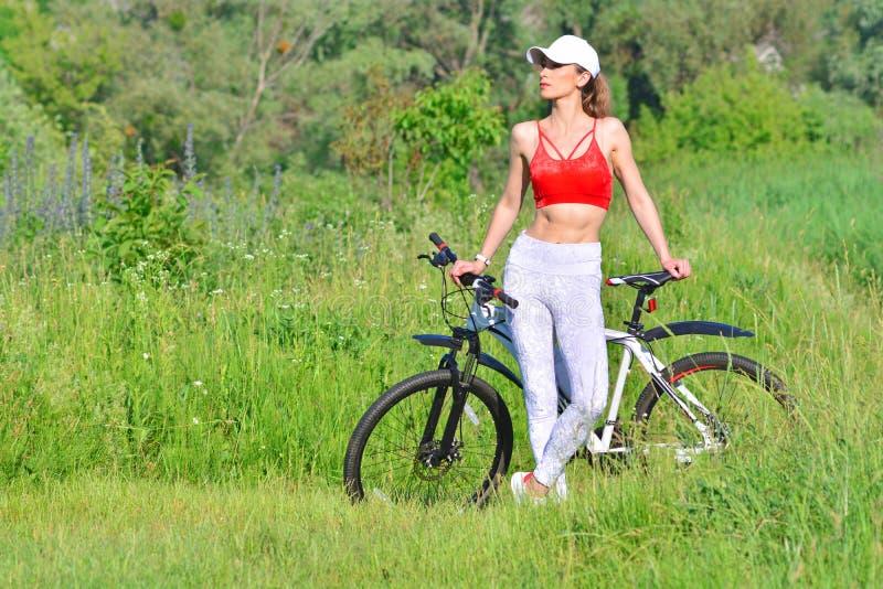 有户外自行车的俏丽的健身妇女 免版税图库摄影