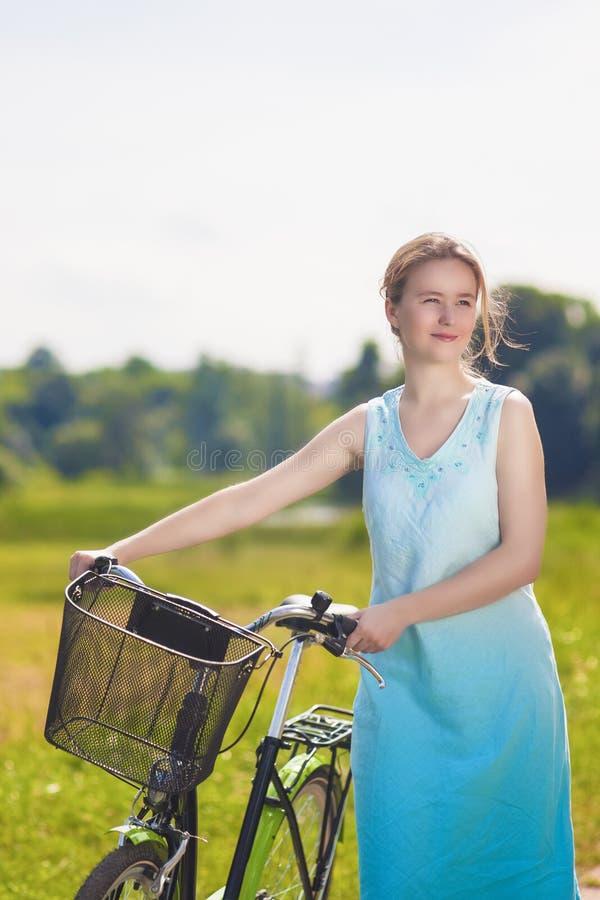 有户外自行车的美丽的白肤金发的妇女 免版税库存图片