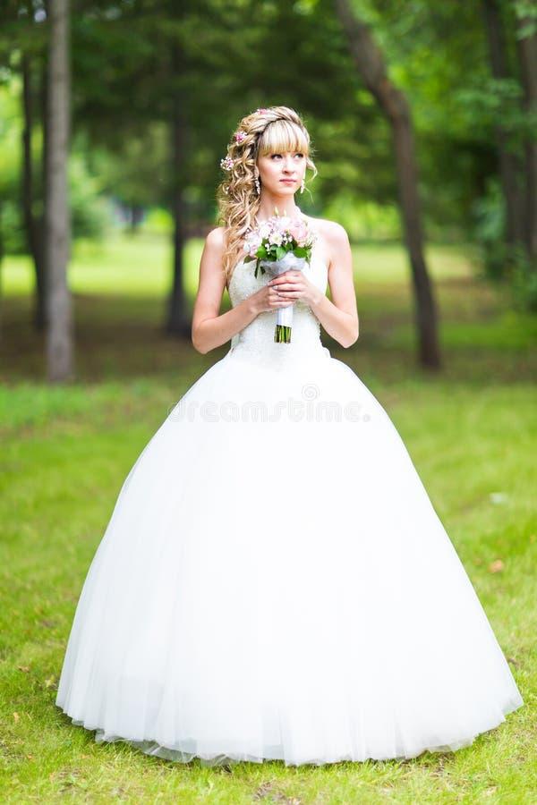 有户外花婚礼花束的美丽的新娘在绿色公园 库存照片