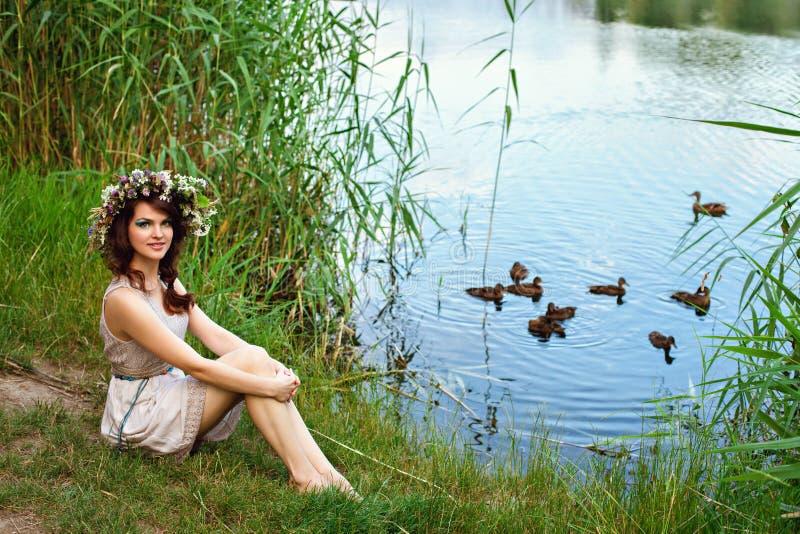 有户外花花圈的年轻美丽的妇女 库存照片