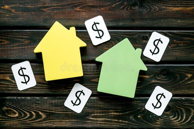 有房子形象和美元的符号的购买房子在办公桌木背景顶视图 库存照片