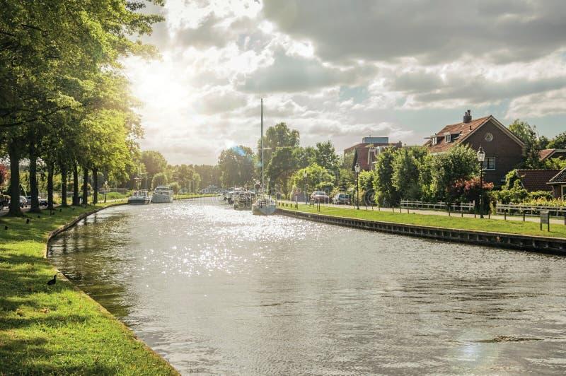 有房子的宽沿途有树的运河和日落小船和亮光在水中反射了在韦斯普 库存图片