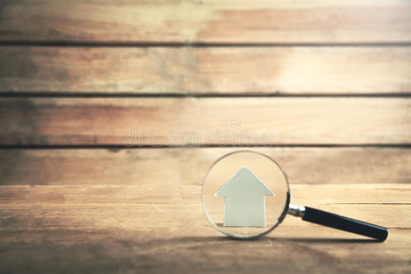 有房子的放大镜木背景的 物产inspe 免版税库存照片