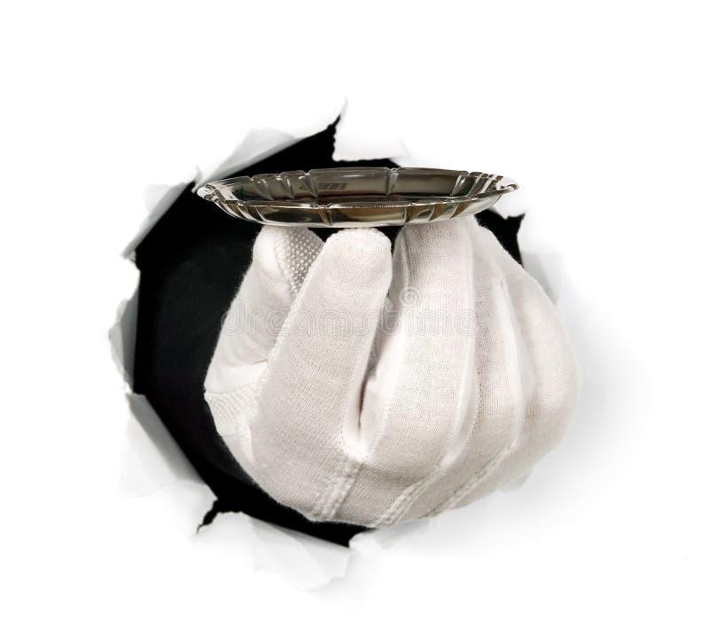有手套的人通过孔拿着在他的手指的盘子 免版税库存图片