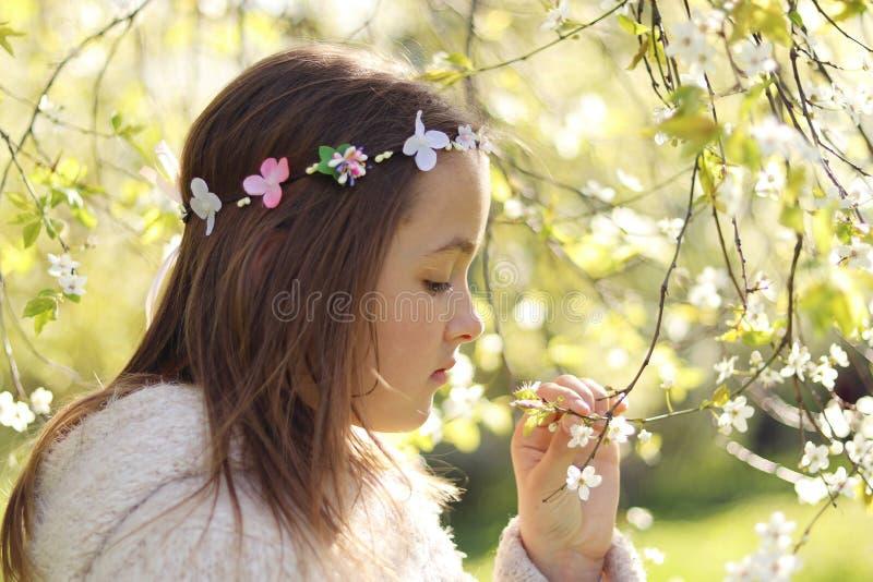 有手工制造头发花圈的逗人喜爱的矮小的沉思女孩在她顶头嗅到在春天开花庭院开花 库存图片