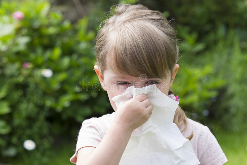 有手帕的逗人喜爱的小女孩在庭院里 免版税库存图片