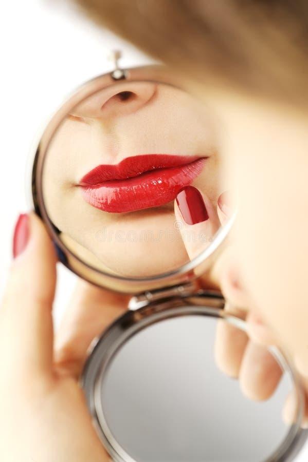 有手手镜的性感的红色嘴唇 免版税图库摄影