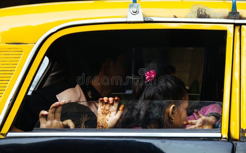 有手拿着一辆传统黄色和黑孟买,印度出租汽车的玻璃窗的无刺指甲花纹身花刺的女孩 免版税库存照片