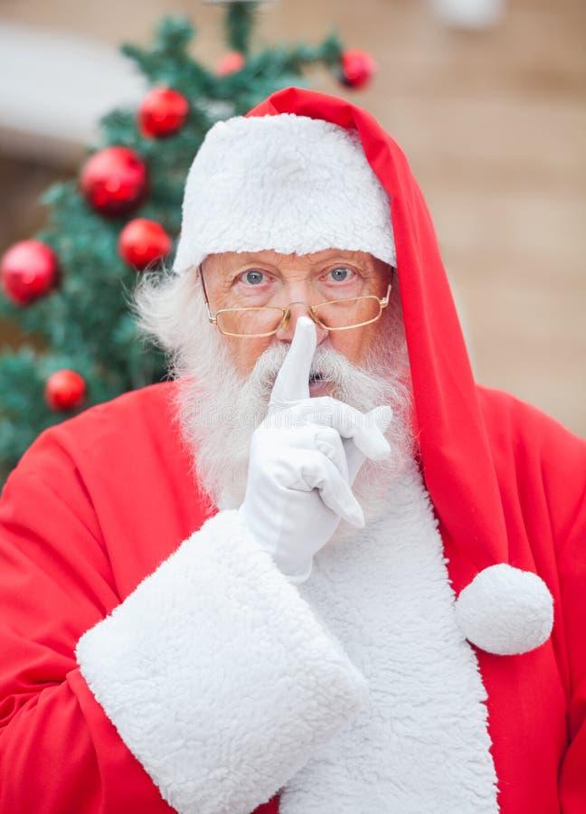 有手指的圣诞老人在嘴唇 库存图片