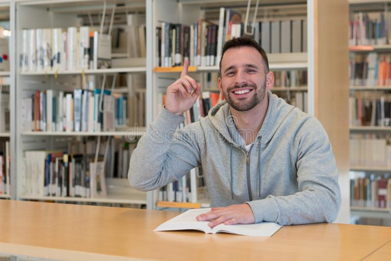 有手指的年轻人满意和微笑对在桌上的一本书在图书馆里 库存图片