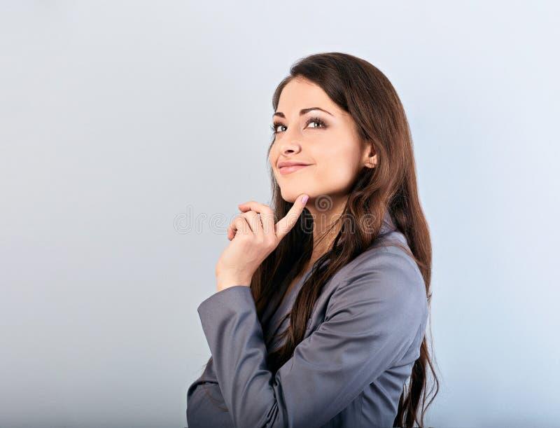 有手指的美丽的年轻愉快的女商人在面孔下和看想出在灰色衣服和长发的 r 免版税库存照片