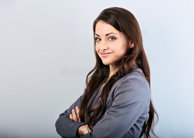 有手指的美丽的年轻愉快的成功女商人在面孔下认为和看在灰色衣服和长发的 免版税库存照片