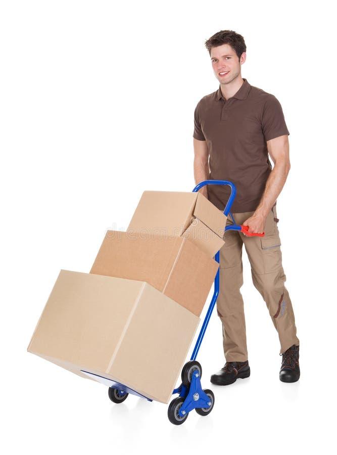 有手推车和箱子的送货人 免版税库存照片