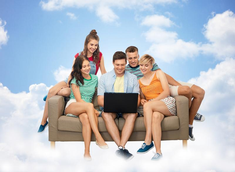 有手提电脑的朋友在云彩的沙发 免版税库存照片