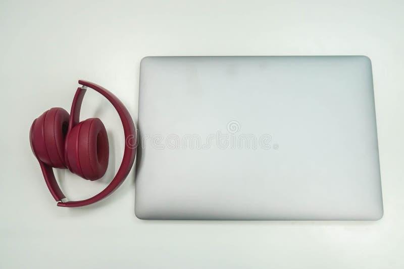 有手提电脑的被隔绝的可折叠的逗人喜爱的桃红色耳机工作的在办公室 免版税库存图片