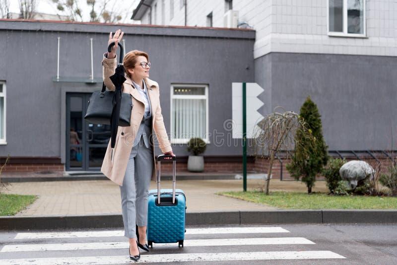 有手提箱和伞的女实业家呼吁出租汽车 库存图片