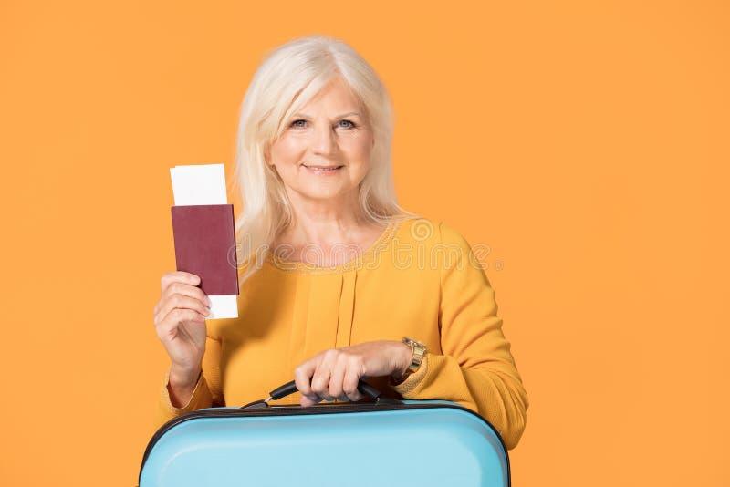 有手提箱和护照的微笑的资深妇女 免版税库存图片