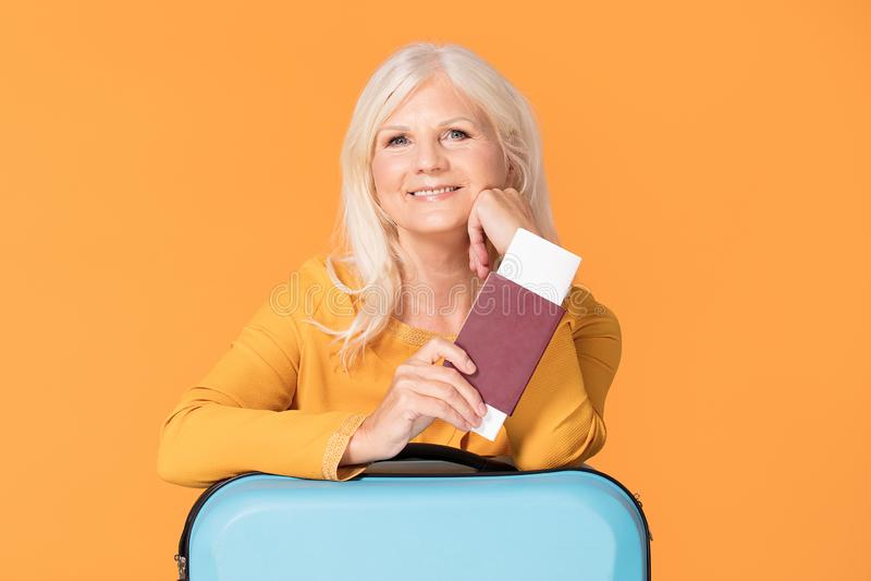 有手提箱和护照的微笑的资深妇女 免版税库存照片