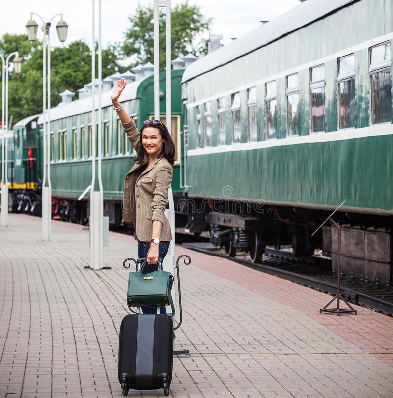 有手提箱和提包的微笑的美丽的中年妇女 免版税库存图片