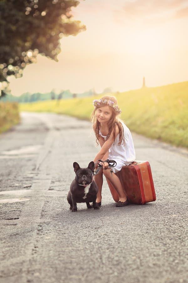 有手提箱和狗的少女 库存照片