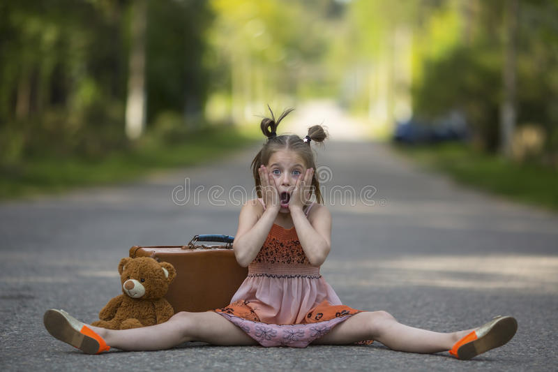 有手提箱和玩具熊的小女孩坐路 免版税库存照片