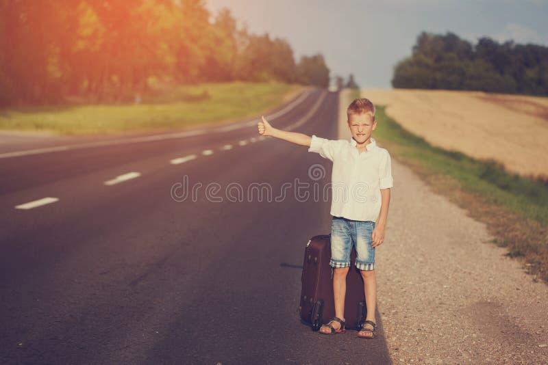 有手提箱旅行的搭车的微笑的孩子 免版税库存图片