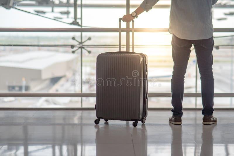 有手提箱行李的年轻人在机场终端 免版税库存图片