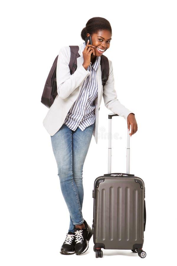 有手提箱身分的愉快的年轻黑人妇女反对被隔绝的白色背景,当谈话在手机时 图库摄影