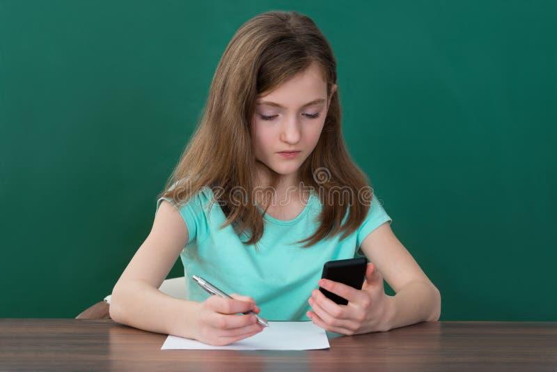 有手机和书的女孩 免版税图库摄影