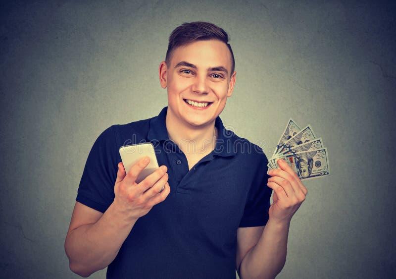有手机和金钱的愉快的人 免版税图库摄影